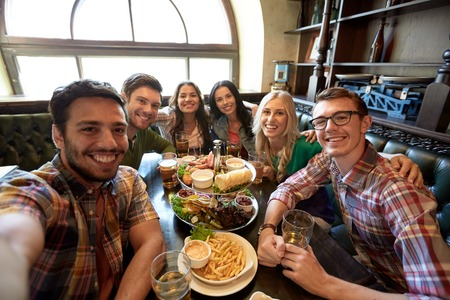 Photo for people, leisure, friendship and technology concept - happy friends taking selfie, drinking beer and eating snacks at bar or pub - Royalty Free Image