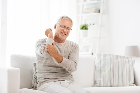 Photo for people, healthcare and problem concept - unhappy senior man suffering from elbow pain at home - Royalty Free Image