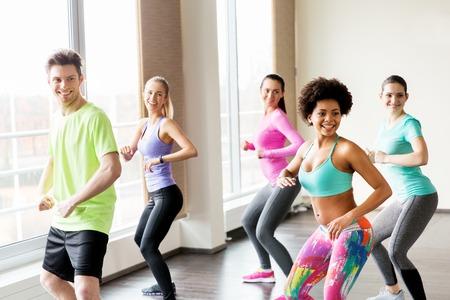Foto de fitness, sport, dance and lifestyle concept - group of smiling people with coach dancing in gym or studio - Imagen libre de derechos
