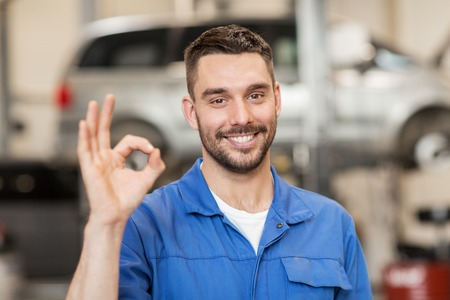 Foto de car service, repair, maintenance and people concept - happy smiling auto mechanic man or smith showing ok hand sign at workshop - Imagen libre de derechos