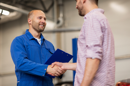 Photo pour auto service, repair, maintenance, gesture and people concept - mechanic with clipboard and man or owner shaking hands at car shop - image libre de droit