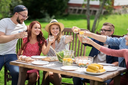 Foto de leisure, holidays, eating, people and food concept - happy friends clinking glasses and celebrating at summer garden party - Imagen libre de derechos