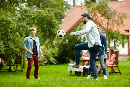 Photo for leisure, holidays, people and sport concept - happy friends playing football at summer garden party - Royalty Free Image