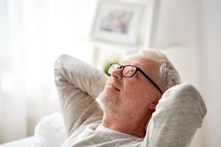 Photo pour old age, comfort and people concept - smiling senior man in glasses relaxing on sofa at home - image libre de droit