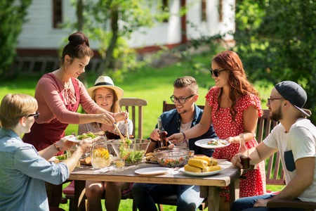 Foto de leisure, holidays, eating, people and food concept - happy friends having dinner and sharing salad at summer garden party - Imagen libre de derechos