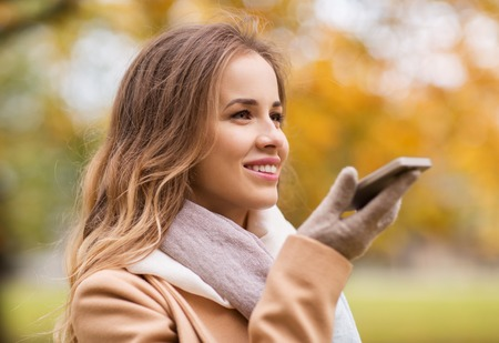 Photo pour season, technology and people concept - beautiful young woman walking in autumn park and using voice command recorder on smartphone - image libre de droit