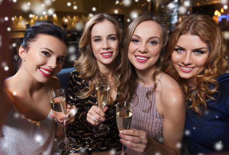 Photo for friends, bachelorette party, technology and holidays concept - happy smiling young pretty women with champagne glasses taking selfie at night club - Royalty Free Image