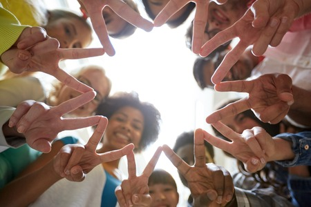 Foto de education, friendship, gesture, victory and people concept - group of happy international students or friends standing in circle and showing peace or v sign - Imagen libre de derechos