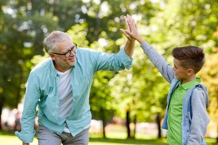 Foto de family, generation, gesture and people concept - happy grandfather and grandson making high five at summer park - Imagen libre de derechos