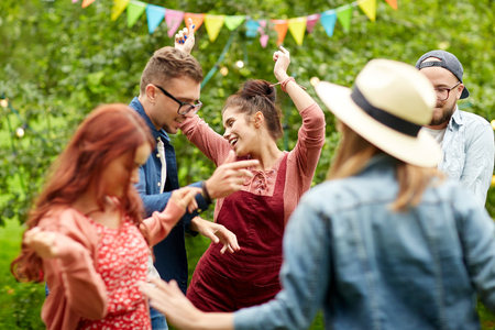 Photo for leisure, holidays, fun and people concept - happy friends dancing at summer party in garden - Royalty Free Image