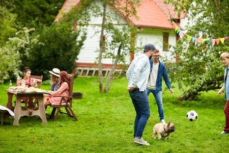 leisure, holidays, people and pets concept - happy friends playing football with dog at summer garden party