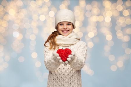 Photo pour people, christmas, holidays, charity and love concept - smiling teenage girl in winter clothes with small red heart over lights background - image libre de droit