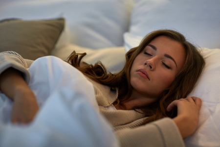 Photo pour night, rest, comfort and people concept - young woman sleeping in bed at home - image libre de droit
