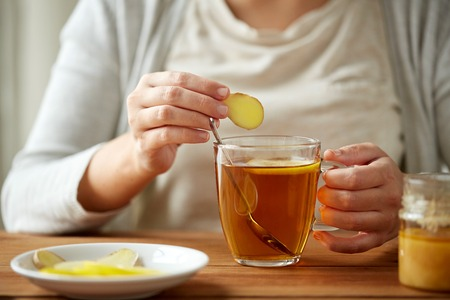 Photo for health, traditional medicine and ethnoscience concept - close up of woman adding ginger to tea cup with lemon and honey - Royalty Free Image