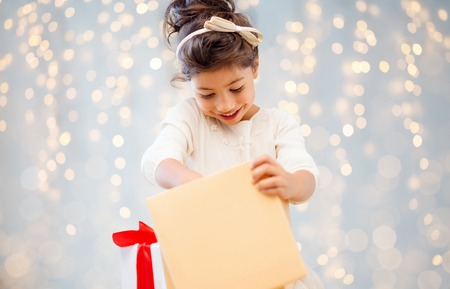 Photo for holidays, christmas, childhood and people concept - smiling little girl with gift box over lights background - Royalty Free Image