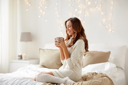 Photo pour morning, leisure, christmas, winter and people concept - happy young woman with cup of coffee or tea in bed at home bedroom - image libre de droit
