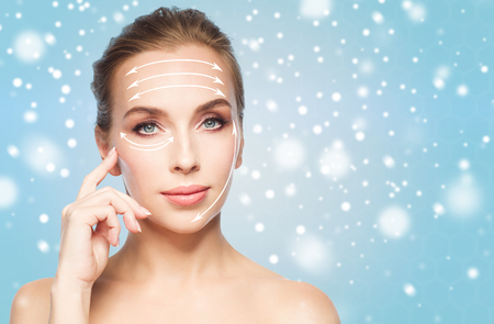 Foto de beauty, people , plastic surgery and anti-age concept - beautiful young woman with lifting arrows on face over blue background and snow - Imagen libre de derechos