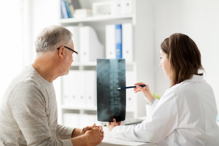 Photo pour medicine, healthcare, surgery, radiology and people concept - doctor showing x-ray of spine to senior man at hospital - image libre de droit