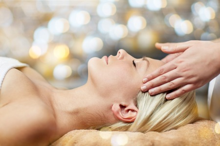 Foto de people, beauty, spa, healthy lifestyle and relaxation concept - close up of beautiful young woman lying with closed eyes and having face or head massage in spa - Imagen libre de derechos