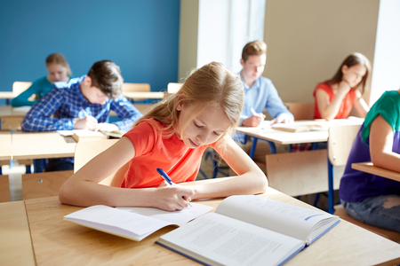 Photo pour education, learning and people concept - student girl with book writing school test - image libre de droit