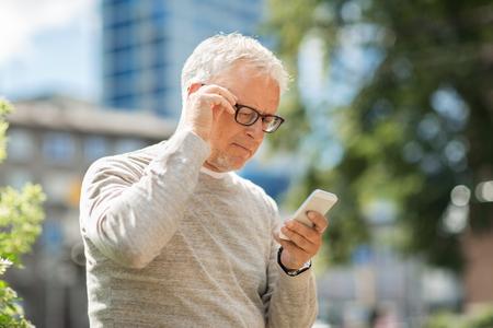 Foto de technology, people, lifestyle and communication concept - senior man texting message on smartphone in city - Imagen libre de derechos