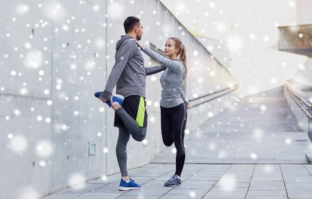 fitness, sport, people and healthy lifestyle concept - smiling couple of sportsmen stretching leg outdoors over snow