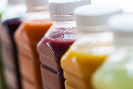Photo for healthy eating, drinks, diet and detox concept - close up of plastic bottles with different fruit or vegetable juices - Royalty Free Image