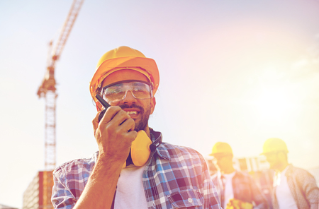 Photo pour industry, building, technology and people concept -male builder in hardhat with walkie talkie or radio at construction site - image libre de droit