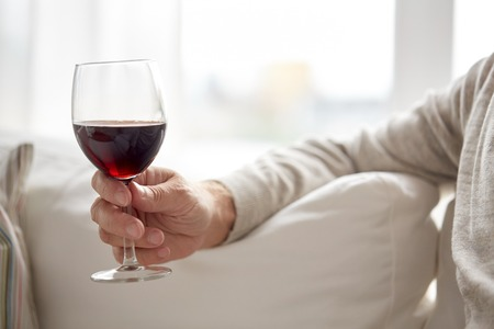 Foto de people, alcohol and drinks concept - close up of senior man hand holding glass with red wine at home - Imagen libre de derechos