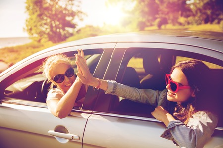 Photo pour summer vacation, holidays, travel, road trip and people concept - happy teenage girls or young women in car at seaside making high five gesture - image libre de droit