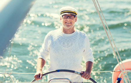 Photo pour sailing, age, tourism, travel and people concept - happy senior man in captain hat on steering wheel and navigating sail boat or yacht floating in sea - image libre de droit