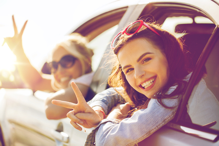 Photo pour summer vacation, holidays, travel, road trip and people concept - happy teenage girls or young women in car at seaside - image libre de droit