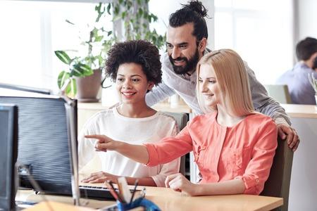 Foto de business, startup and people concept - happy creative team networking with computer in office - Imagen libre de derechos