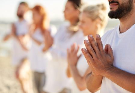 Foto de group of people making yoga or meditating on beach - Imagen libre de derechos