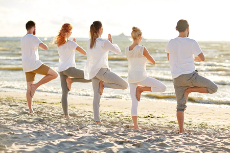 Photo pour group of people making yoga in tree pose on beach - image libre de droit