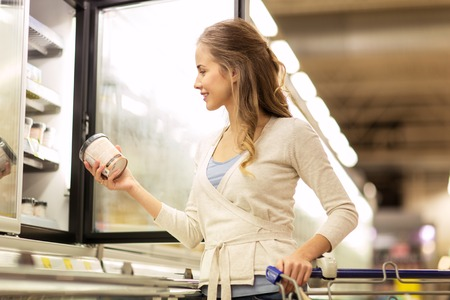 Photo for woman with ice cream at grocery store freezer - Royalty Free Image