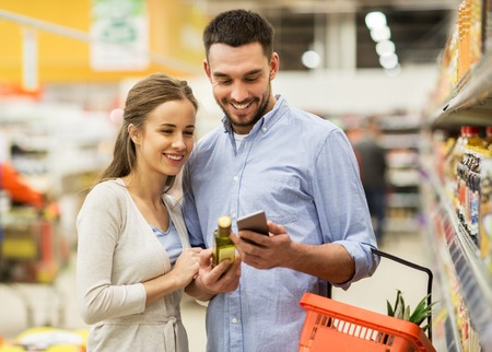 Photo pour couple with smartphone buying olive oil at grocery - image libre de droit