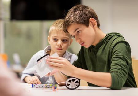 Photo pour education, children, technology, science and people concept - happy boys building robots at robotics school lesson - image libre de droit