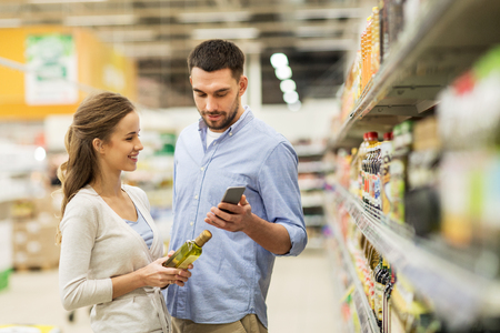 Photo pour shopping, food, sale, consumerism and people concept - happy couple with smartphone buying olive oil at grocery store or supermarket - image libre de droit