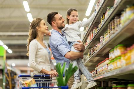 Foto de family with food in shopping cart at grocery store - Imagen libre de derechos