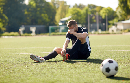 Photo for injured soccer player with ball on football field - Royalty Free Image