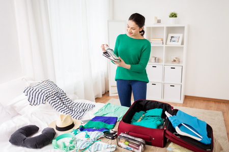 Photo pour woman packing travel bag at home or hotel room - image libre de droit