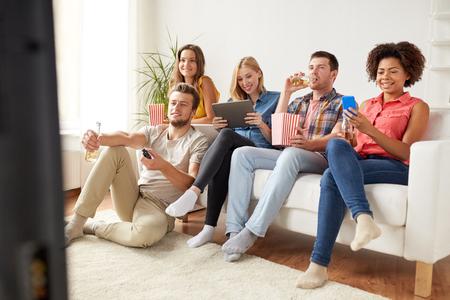 Foto de friends with gadgets and beer watching tv at home - Imagen libre de derechos