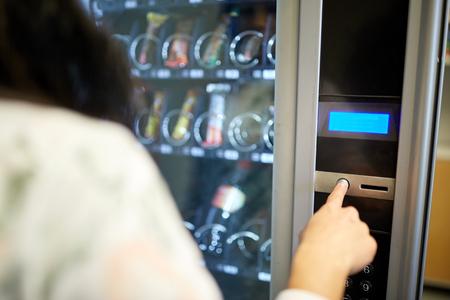 Photo pour woman pushing button on vending machine - image libre de droit