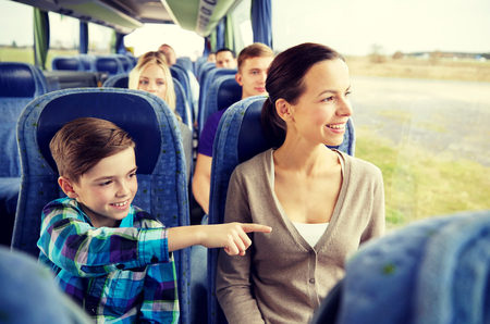 Foto per travel, tourism, family, technology and people concept - happy mother and son riding in travel bus - Immagine Royalty Free