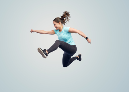 Foto de sport, fitness, motion and people concept - happy smiling young woman jumping in air over blue background - Imagen libre de derechos
