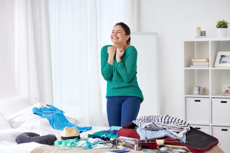 Photo pour happy woman packing travel bag at home - image libre de droit