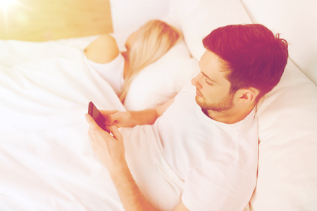 Photo pour man texting message while woman is sleeping in bed - image libre de droit