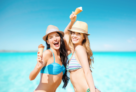 Foto de smiling women eating ice cream on beach - Imagen libre de derechos
