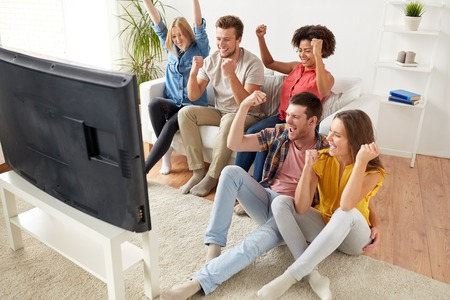 Photo for happy friends with remote watching tv at home - Royalty Free Image